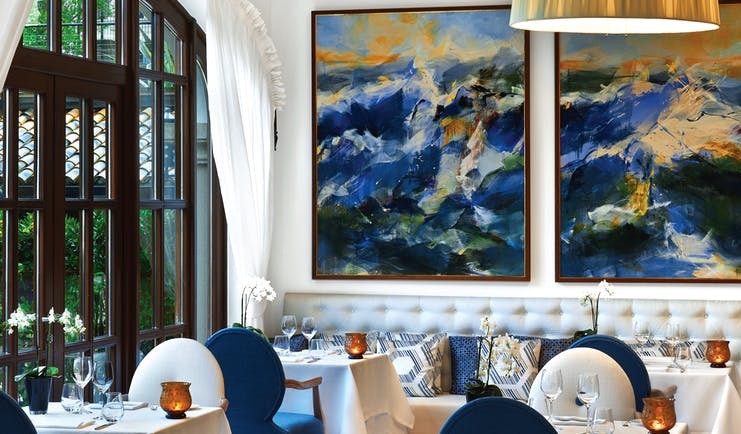 Aqua restaurant with paintings on the walls and blue and white coloured chairs set up