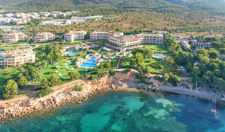 Birds eye view of resort showing proximity to cliff and ocean with large pools and buildings