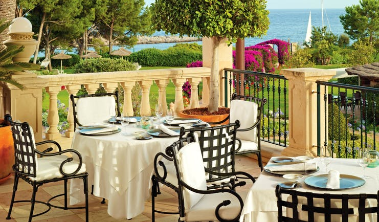Outdoor dining terrace with tables and chairs set out overlooking trees and the sea