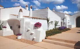 Torralbenc Menorca hotel exterior white buildings pink flowers pathways