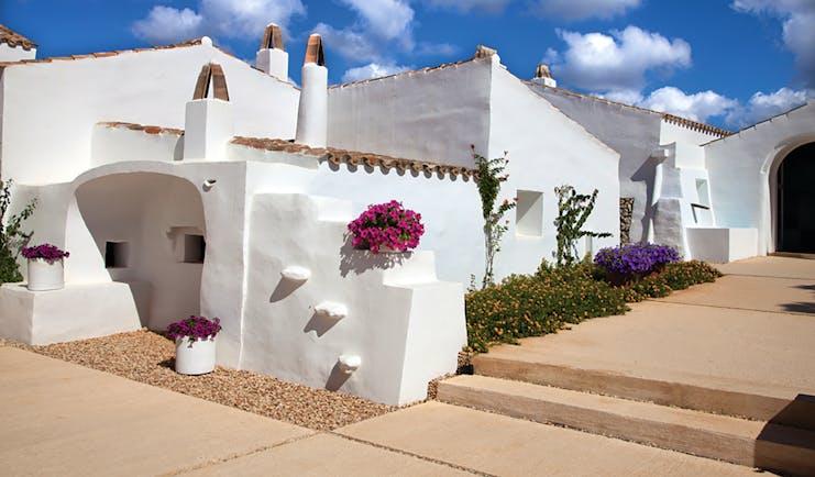Torralbenc Menorca hotel exterior white buildings pink flowers pathways