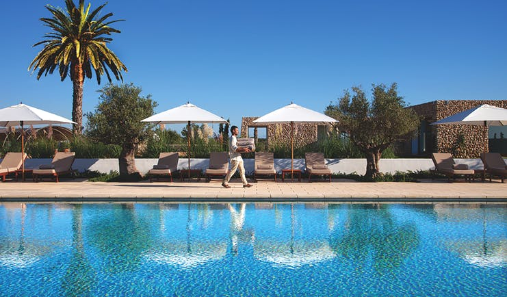 Torralbenc Menorca pool sun loungers umbrellas palm trees