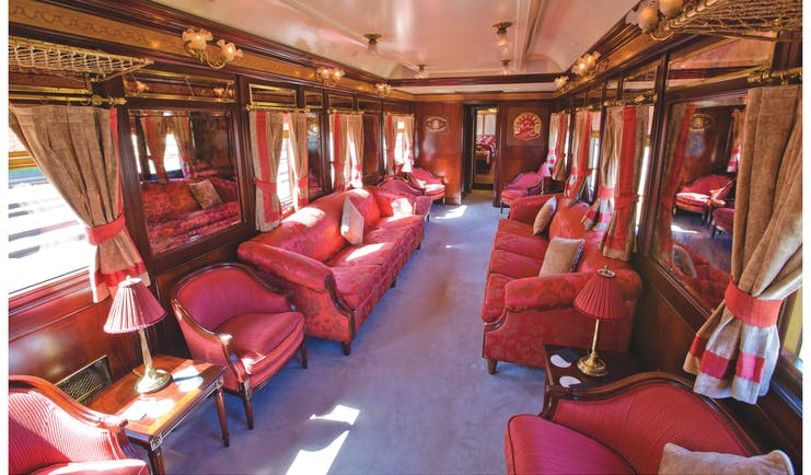 Red sofas and chairs in train carriage