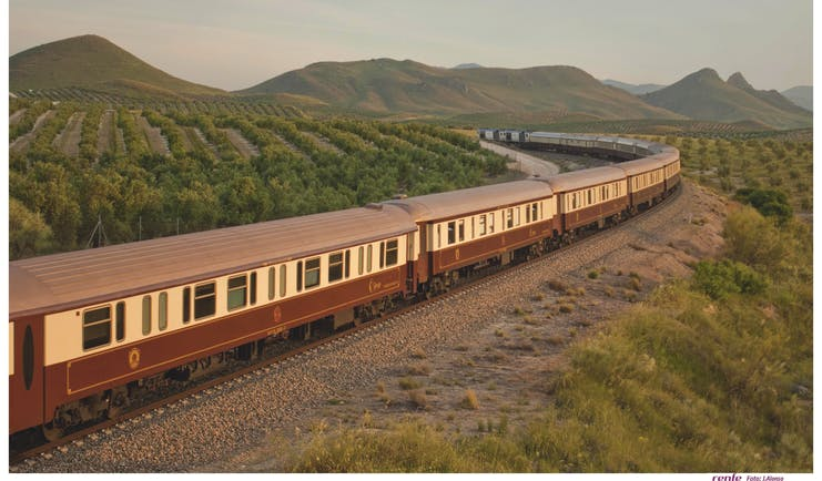 Brown and beige train on track through southern Spanish landcsape