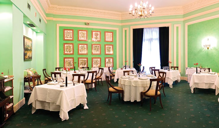 Restaurant with green walls, chandeliers and tables set out