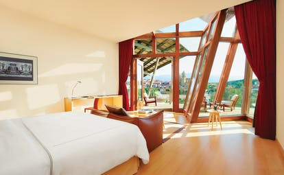 Suite with double bed, seating areas and views over the mountains