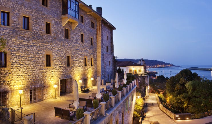 Panoramic view from the hotel with views over the ocean and stone buildings at dusk