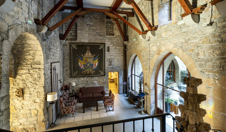 Reception area with large stone walls, arched doorways leading to an outdoor terrace and sofas inside