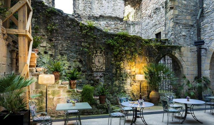 Outdoor terrace area with tables and chairs, lamps lighting up the stone walls and vines growing up them