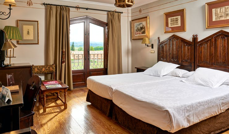Standard double room with two double beds laid side by side, wooden doors opening onto a balcony with views over fields