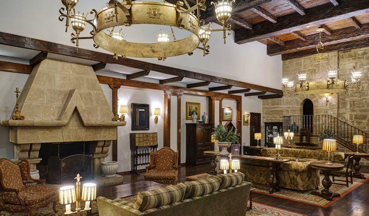 Lounge area with high ceilings, fireplace, large chandeliers, sofas and armchairs
