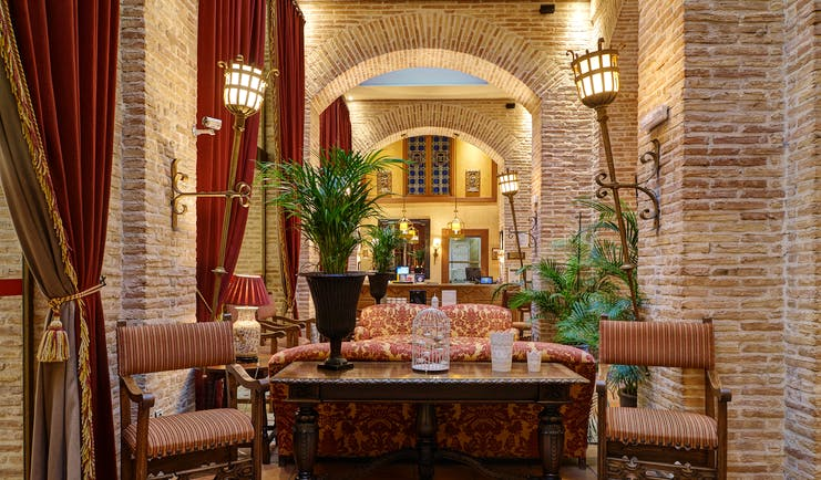 Reception with high ceilings and archways, arm chairs and sofas laid out for seating and potted plants scattered around the room