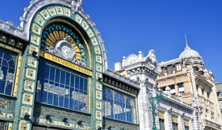 Ornate and elaborate facade with glass panels and green and yellow tiles of the Abando railway station in Bilbao