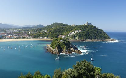 Sailing boats on blue sea in front of small island in bay with yellow sand beach in background at San Sebastian