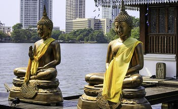 Four golden buddhas on edge of a lake