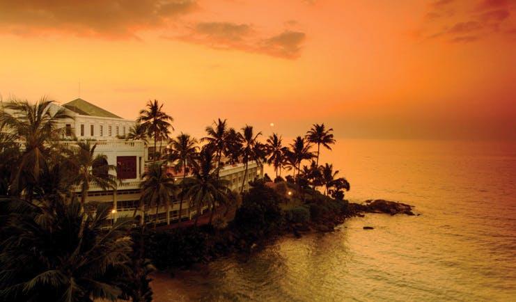 Mount Lavinia Hotel Sri Lanka exterior white hotel next to sea palm trees sunset
