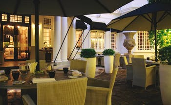 Paradise Road Tintagel dining terrace, tables and chairs under umbrellas on patio