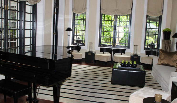 Paradise Road Tintagel lounge with sofas and chairs, piano, monochrome decor