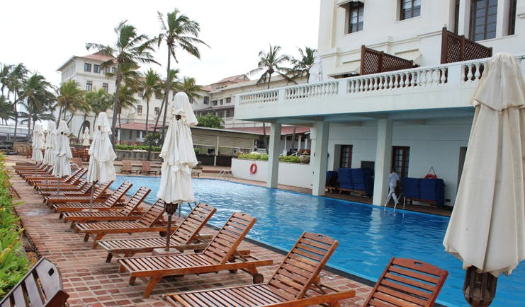 Galle Face Hotel Sri Lanka poolside wooden sun loungers and umbrellas