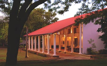 Cinnamon Lodge Sri Lanka nighttime sloping roof red and white colonnaded building