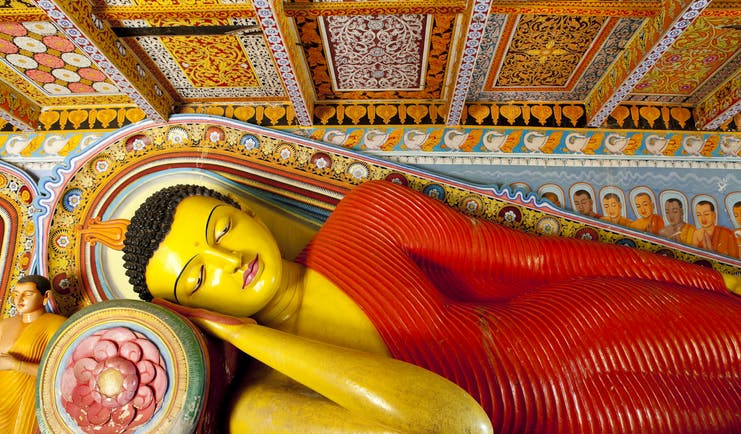 Isurumuniya temple in the Cultural Triangle, colourful buddha statue of Buddha reclining, intricate details