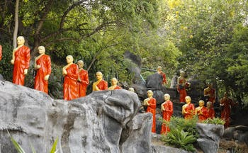 Monk statues, dressed in orange, lining the hillside at the Golden Temple in the Cultural Triangle