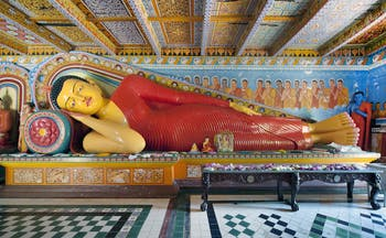 Reclining Buddha at Isurumuniya Temple, intricate colourful carving, colourful room