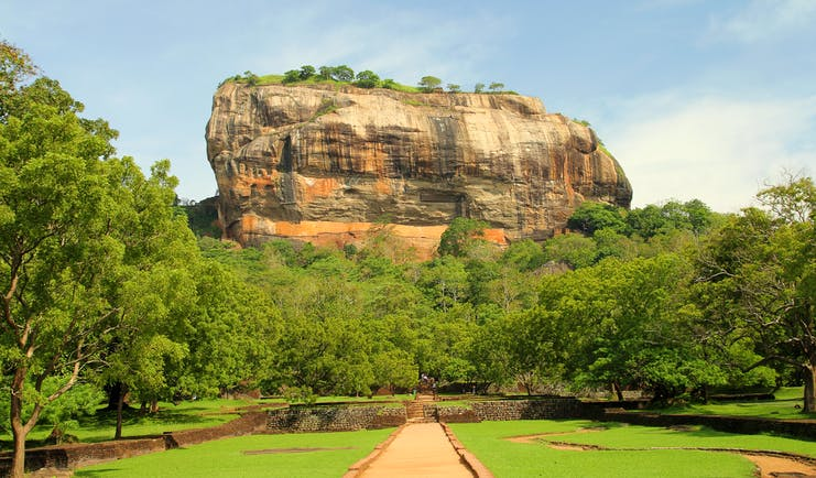 Sigiriya rock in background, trees and grass in foreground