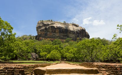 Sigiriya rock surrounded by trees and grassland