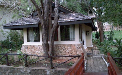 Deer Park Sri Lanka cottage bridge entrance wooden bridge to white and stone cottage