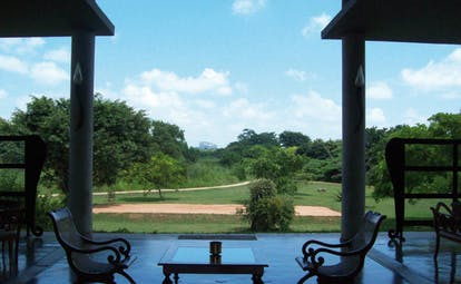 The Elephant Corridor Sri Lanka patio with two chairs and view of gardens with trees