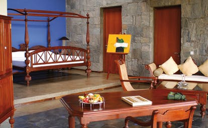 The Elephant Corridor Sri Lanka suite with four poster bed stone walls easel with art lounge area