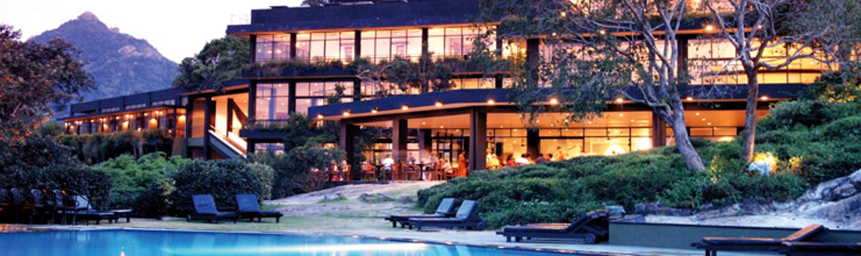 Heritance Kandalama Sri Lanka outdoor pool loungers trees and hotel with large windows sunset