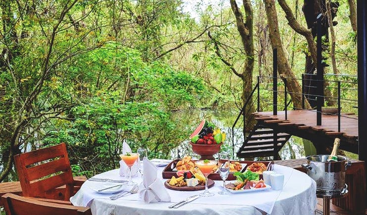 Kalundewa Retreat table on terrace set ofr breakfast with pastries and fresh fruit, views over lake and tree tops