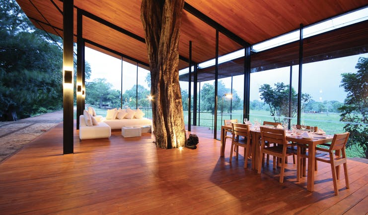 Kalundewa Retreat lobby, covered terrace with tree growing in centre, sofa, tables, views of surrounding countryside