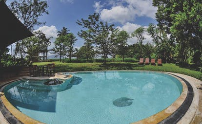Kalundewa Retreat pool, surrounded by lawns, sun loungers