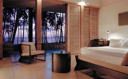 Amanwella Sri Lanka suite bedroom chaise longue chair patio palm trees at sunset