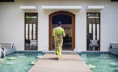 Anantara Peace Haven Tangalle Sri Lanka spa entrance walkway over water feature woman