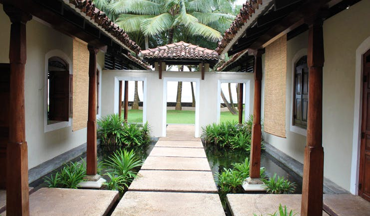 Apa Villa Thalpe Sri Lanka walkway with white and brown buildings