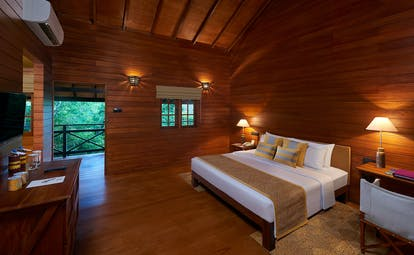 Cinnamon Wild beach chalet, double bed, dresser, wooden walls and ceiling, balcony with tree views