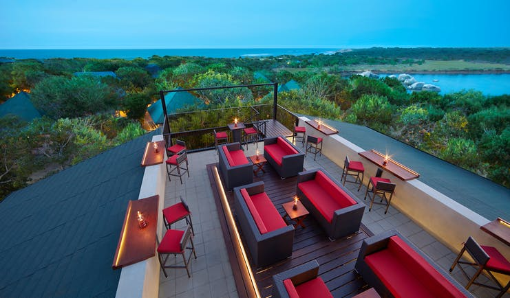 Cinnamon Wild rooftop terrace bar, tables and chairs, sofas, views over countryside, sea in background