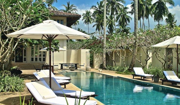 Elysium Villa Sri Lanka poolside sun loungers umbrellas trees