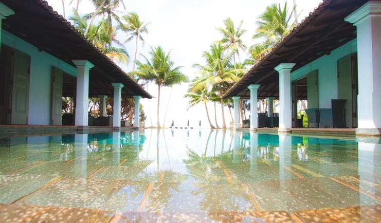 Era Beach Hotel pool, surrounded by columns, palm trees in background