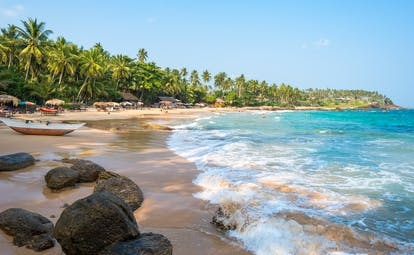 Beach in Tangalle, waves lapping golden sand, umbrellas and sun loungers, wooden boat, people swimming in the sea