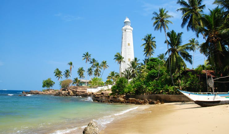 Dondra lighthouse on the South Coast, white lighthouse, palm trees, sand, ocean