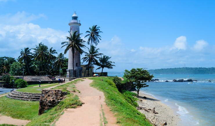 Lighthouse overlooking sea in Galle, palm trees, beach