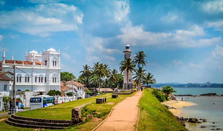 Lighthouse on the seafront in Galle, beach, waves, islands in backgrounds