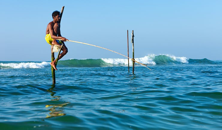 A stilt fisherman sitting on stilts in the sea, fishing for fish