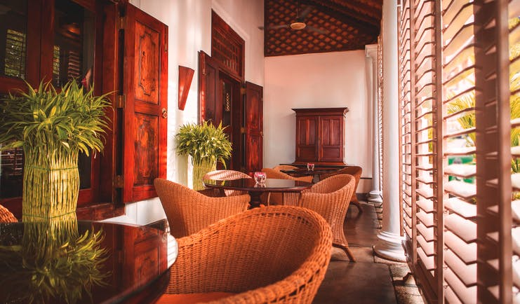 Galle Fort Hotel verandah, indoor sitting area, wicker tables and chairs, colonial style decor