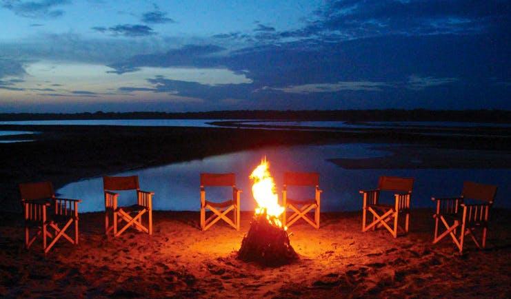 Mahoora Luxury Safari Camps Sri Lanka campfire chairs lake in background